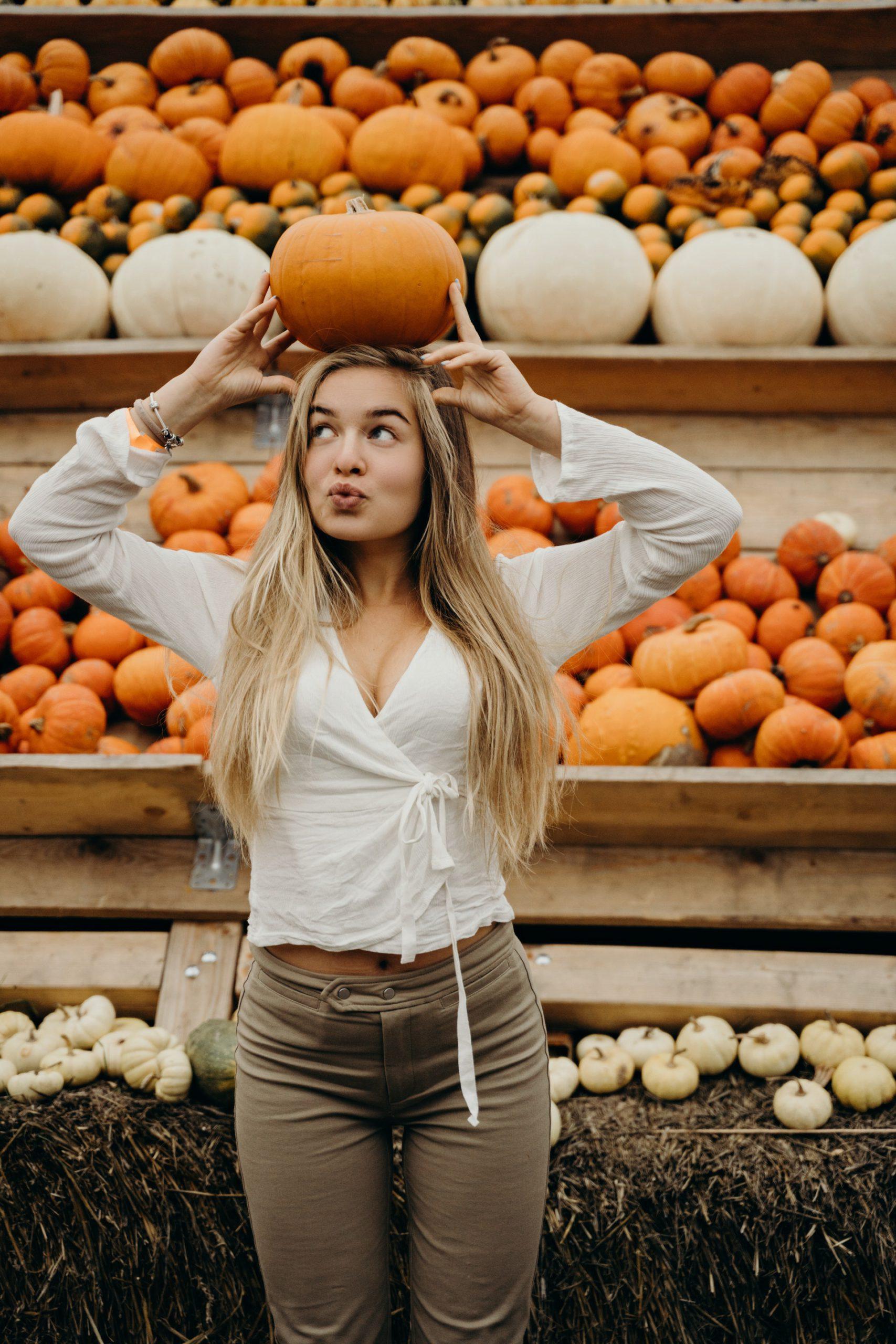 Photo of Girl Balancing a Pumpkin on Her Head