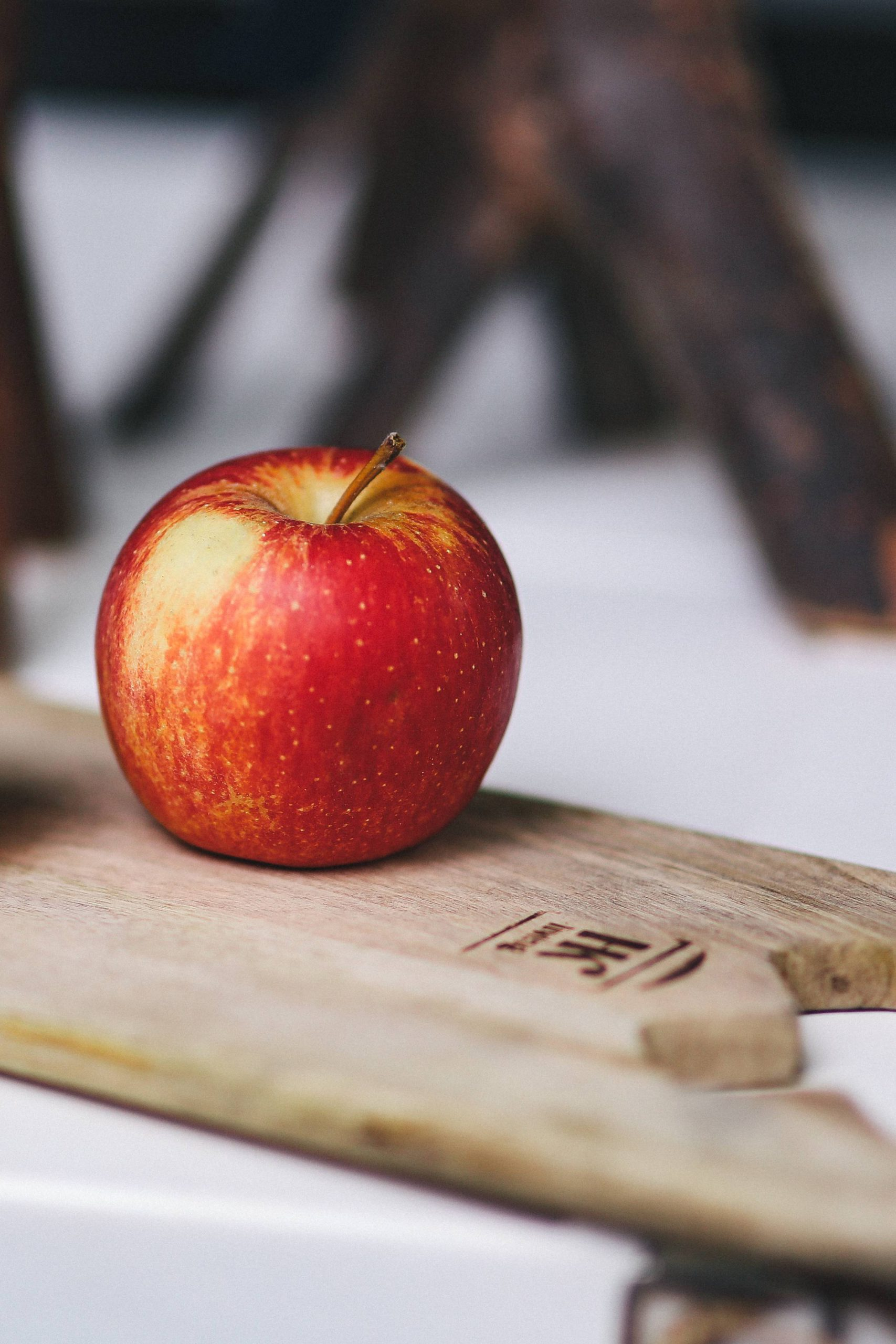 Photo of a Single Red Apple on a Wooden Board